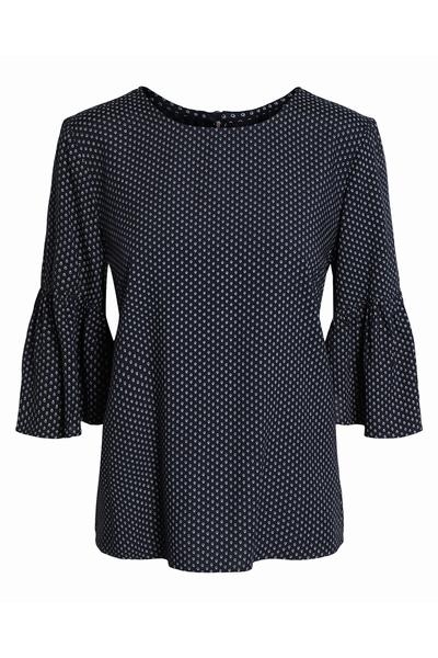Cette blouse à pois est conçue avec une encolure ronde et